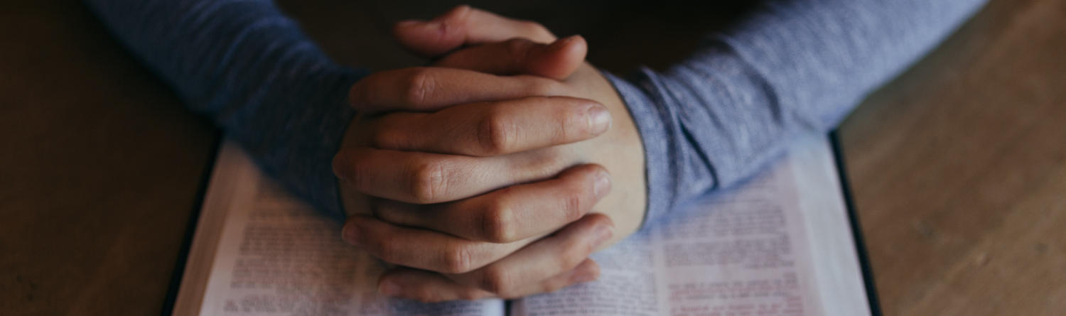 Hands folded in prayer on top of Bible